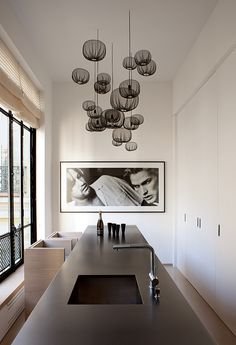 A large Sam Samore photograph presides over the sleek custom kitchen. The chandelier is by Nendo, one of Yovanovitch's favorite contemporary studios. ''It's minimal but poetic,'' he says. NYTimes-Jean François-Jaussaud