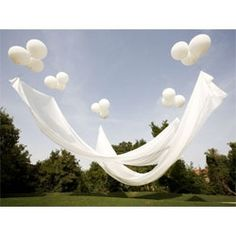 Helium balloons float shade cloths to create a very elegant outdoor gathering space. Use fishing wire and golf tees.