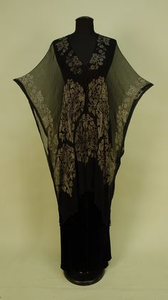 Front View STENCILLED BLACK SILK GAUZE TUNIC, 1920's. Probably Gallenga, square cut wrap with silver Renaissance style trees and stylized creatures, black Venetian glass beads along hem, knotted cord closure with glass bead tassels. 32 x 33.