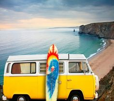 Yellow VW bus by the beach and a surfboard