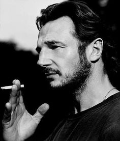 Liam Neeson smoking a cigarette (or weed)