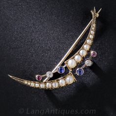 A marvelous and unusual variation on the late 19th century crescent motif, this delightful brooch deconstructs the shimmering pearl crescent mid arc and punctuates it with floating diamonds, sapphires and rubies. Hand-crafted in England in 15 carat gold, with English hallmarks and a rich antique patina.
