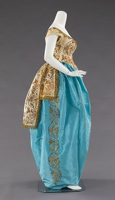 Fancy dress costume (side view) | Charles Frederick Worth (English, 1825-1895) | France, circa 1870 | Cream and blue silk taffeta, gold metallic, white silk tulle | This rare costume is in fact an authentic Turkish woman's ensemble, heavily embroidered in gold by Turkish artisans, that was refashioned at the House of Worth into the form-fitting silhouette of the 1870's | The Metropolitan Museum of Art, New York