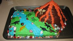 Dinosaur Themed Cake I Made for a 3 year old birthday - used the top of one of those giant cupcake molds for the volcano, the rocks are chocolate, and the dinosaurs are little toys from the party store! He loved it!