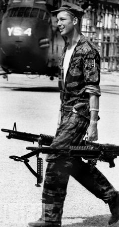 Larry Burrows, Crew chief Farley carries M-60 machine guns to copter