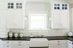 Black counter farmhouse sink marble subway tile backsplash white kitchen cabinet