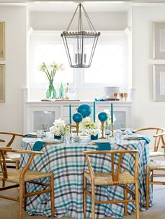 Blue tapers and glass ornaments atop brass candlesticks adorn this Christmas table.