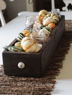 Rustic fall-themed table centerpiece with pumpkins and mason jars in a wooden box #wedding #tablecenterpiece #rustic #fall #autumn