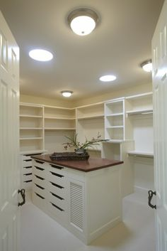 Walk-in closet with multiple shelves and island dresser