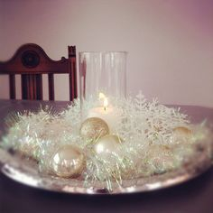 Put It All Together: Your guests will never guess that your holiday decorations came from the dollar store when you pair matching items together, creating really special arrangements for only a few dollars. Here, a silver plastic tray, a length of shiny garland, some plastic ornaments and snowflakes, and a vase with a votive tucked inside transform into a lovely Winter table centerpiece.
