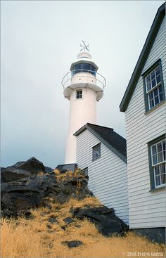 Lobster Cove LIght, Newfoundland  1897. Active; focal plane 35 m (115 ft); white flash every 4 s. 8 m (28 ft) cylindrical cast iron tower with lantern and gallery, painted white. 2-story wood keeper's house now used as a national park visitor center and museum.