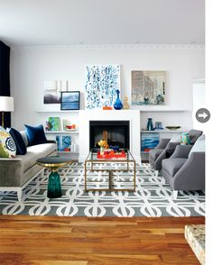 A graphic rug anchors this living space with a neutral tone of grey accented with blues. Designed by Samantha Pynn (via Style at Home).