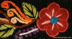 Acercamiento del bordado hecho a mano por artesanos ayacuchanos (Perú) sobre tela tejida en telar con fibras naturales.