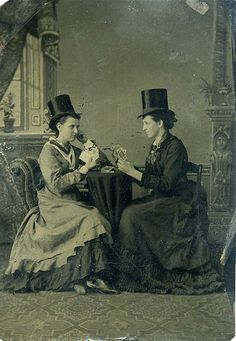victorian ladies in top hats, playing cards & smoking cigars, this is likely an image where the women are pretending to be men, whatever the reason.