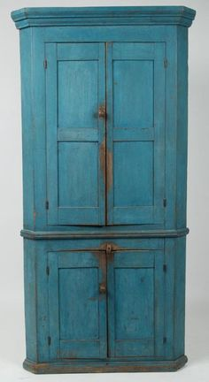 "Sold $2,900  BEDFORD CO., PENNSYLVANIA PAINTED POPLAR CORNER CUPBOARD, one-piece construction, a fine diminutive example with well-executed molded cornice above double-paneled upper doors, applied waist moldings, and fielded-panel lower doors, resting on a base with applied moldings. Blue-painted surface. Circa 1830-1850. 75"" H, 35"" W, 24"" corner. Provenance: Collection of the late John and Lil Palmer, Purcellville, VA.  Ex-collection of Skip and Effie Sheppard, PA, 1994."