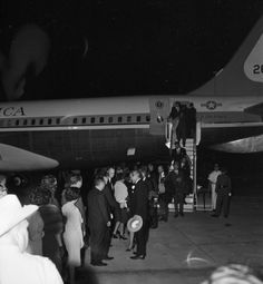 Pres. John F. Kennedy, wife Jackie, Gov. Connally, and others who have de-planed from Air Force One, being greeted by reception line on tarm...