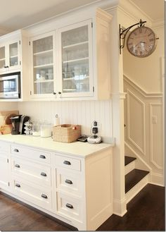 A classic white kitchen. Love the drawer pulls, glass cabinets and the clock.