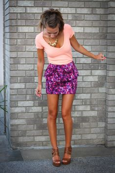 Super cute purple, floral skirt and coral shirt. Love the brown wedges too. The colors pop against her dark tan.