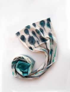 A scarf hand-painted in shades of blue and teal.