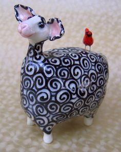 """By Karen Fincannon. This one of a kind, ceramic sheep sculpture is approximately 4 1/2 inches high and 4 inches long. She is all handbuilt from clay. I fire each sheep sculpture once and then paint all the individual """"wool"""" swirls with underglaze. She is then coated with clear glaze and fired again. This happy sheep has a cardinal on her back who's along for the ride, wherever their journey might take them. Thank ewe for stopping by!"""