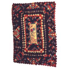 1880-1890 felted wool table rug in a layered clamshell pattern, each row stepping higher toward a central damask panel decorated with appliqued hearts and a floral sprig whose leaves are stuffwork hearts.