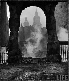 Spires of St. Paul's Cathedral seen through the archway of a smoldering ruin after a Nazi incendiary bomb attack on the city. London, December 1940