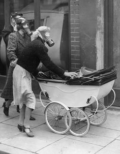 A gas-mask wearing young mother attends to her child's special baby buggy gas protector during a surprise test in Kingston, England ~