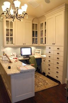 Craft Room... Kitchen cabinetry for craft storage. I like how there is desk space besides where the computer is, within chair swivel range.