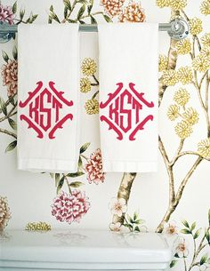 Floral wallpaper and monogrammed hand towels in a bathroom