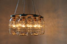 WAGON WHEEL Mason Jar Chandelier - Quart Sized Ball Mason Jar Swag Lighting Fixture - Upcycled Rustic Eco Friendly BootsNGus Lamp Design. $200.00, via Etsy.