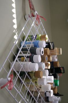 DIY: She used two shelves from one of those wire shelving units and zip tied empty thread spools in all four corners and the middle.
