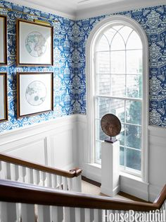 Clarence House's The Vase wallpaper lines the main stairway.