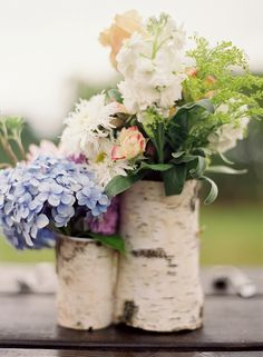 Flower arrangements in birch bark sleeves make simple and rustic centerpieces.