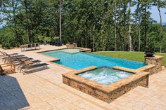 This eye-catching vanishing-edge pool features Oklahoma flagstone coping, a stamped-concrete apron, a white Pebble Tech finish, and two Grand Effects fire/water bowls. The sparkling water retains its crystal beauty with an automated Paramount in-floor cleaning system. Elite Pools by Scott, Little Rock, Arkansas