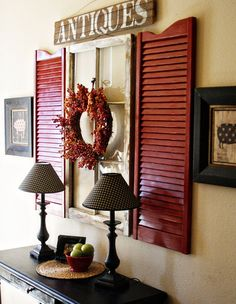 Shutters wall art idea - how unique and totally interesting.  Paint a color to match your decor and pictures.  Look for old windows in antique stores to complete the look.