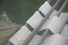Canvas drop cloths woven on top of pergola - hooked on to screws with grommets for easy removal
