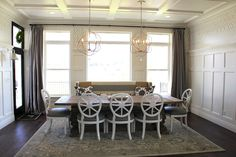 A transitional dining room with white dining chairs with upholstered seats and an old-fashioned wood pedestal dining table
