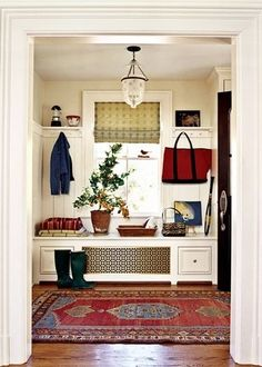 nice entry with seat, hooks and shelf. I would probably put the plant outside, though. :)