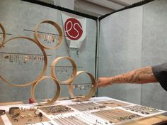 Jewelry display - wooden hoops with wire (thin bars perhaps?) give elevation without much weight, and are easy to see through.  Could screw together for stability and ease of transport.