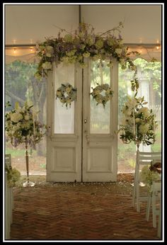 French doors festooned with flowers and beset on either side with tall candelabras. A beautiful vintage-inspired backdrop for your ceremony!
