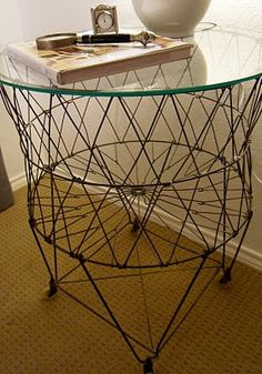 Collapsible Antique Wire Frame Laundry basket repurposed as side table with a piece of tempered glass. Cool