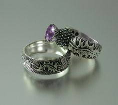 The silver shank is adorned with detailed carvings of thistle's leaves and has a hammered texture. The bezel made in the shape of the thistle's flower is set with a genuine deep purple 8mm Amethyst gem. The ring is stamped with the jeweler's mark and 925 (silver)  Available in sizes from 4 to 9.5.
