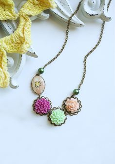 """Blooming Ardesia Indie Necklace 39.99 at shopruche.com. A dark brass chain holds a pretty floral collection of sage, pink, and peach colors.  Chain: 9.5"""" length  Pendant: 0.75"""" length"""