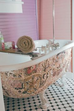 Shell mosaic on the clawfoot tub of a pink bathoom in a Florida beach cottage.