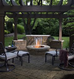 Pergola with fire pit.  I love the wall behind the pit.  The pavers bring it all together and makes it look like a cozy room.