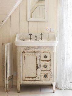 Shabby chic bathroom mirror. Vintage distressed cabinet, flowy white curtains.