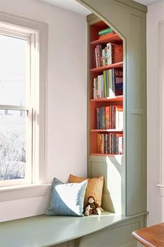 Recessed bookcases come to the fore with a bright orange-red that saturates each shelf area from back to front. The contrast also enhances the built-in's otherwise gray-green surfaces. Similar to shown: Olympic's Light Sage (built-in) and Candy Corn (shelves) | Photo: Eric Roth | thisoldhouse.com