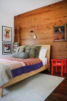 LOVe this room (aside from the bed frame), but the plank wall is great and the pillow shams make me want to go camping.