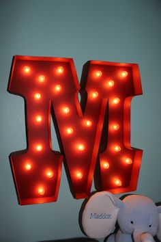 Love the carnival style lighted #red initial  on the #aqua wall  #initial #nursery