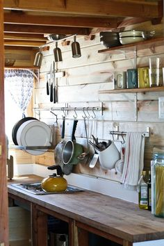Tiny Home on the Range house. Kitchen with wooden counters & rustic exposed beams. Hanging pots & pans. Enamelware.
